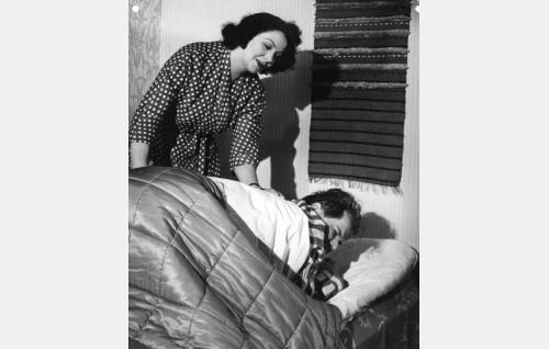 Vaimo (Rauni Luoma) herättelee radiokuuluttajaa (Kauko Kokkonen).