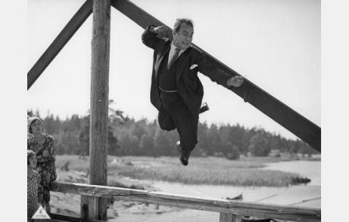 Erkki on nostanut Eetun (Aku Käyhkö) sillannaulaan roikkumaan tukkilaisten ja kyläläisten tappelussa.