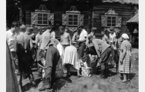 Komppania pysähtyneenä ruokailutauolle Itä-Karjalassa. Oikealla koko kuvauksien ajan mukana seurannut muonaemäntä ja keittäjä. Myöskin näyttelijät, avustajat ja oma henkilökunta ruokailivat kenttäkeittiöstä.