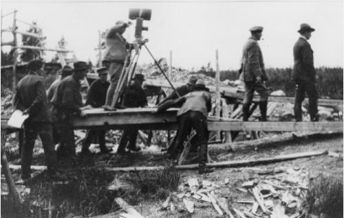 Kamera on nostettu miesvoimin työnnettävälle alustalle. Kameran veivissä Gustaf Boge. Oikealla Einar Rinne ja Urho Somersalmi.