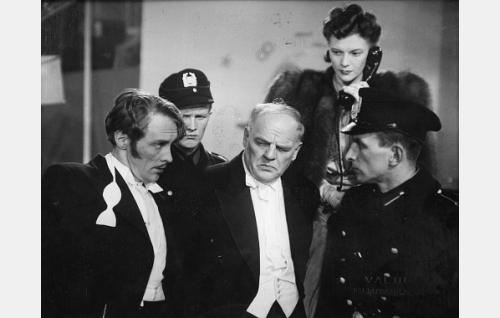Amerikkalainen miljonääri Georg. W. Brown (Yrjö Tuominen) ja hänen yksityissihteerinsä (Jorma Nortimo,vas.) Taustalla toimittaja Eija Taipale (Eija Karipää). Poliisit ovat tunnistamattomia.