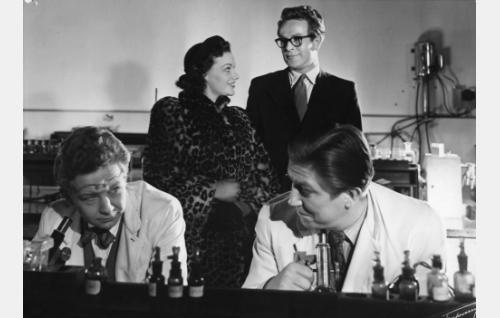Etualalla tohtori Syrjä (Lasse Pöysti) ja laborantti (Arttu Suuntala), heidän takanaan seisovat tanssijatar Kaarina Tuomo (Pirkko Niemelä) ja tohtori Kalle Lehmus (William Markus).