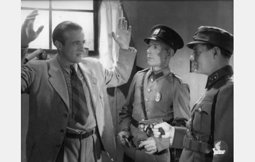 Luutnatti Ville Somero (Matti Lehtelä) ja poliisi (Lennart Vaikonpää) pidättävät vakoilijaksi paljastuneen Kausalaisen (Ensio Jouko).