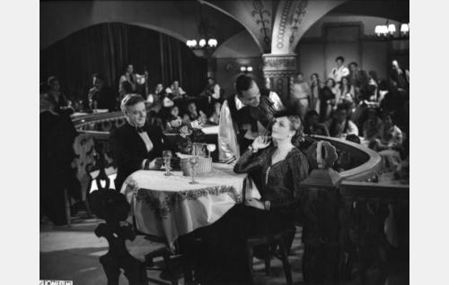 Pöydän ääressä Sven Relander ja Hanna Taini. Viulistia ei ole tunnistettu.