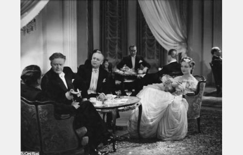 Etualalla istuvat Topo Leistelä, Sven Relander, Arvi Tuomi ja Hanna Taini. Taustalla ikkunan edessä Olavi Reimas.