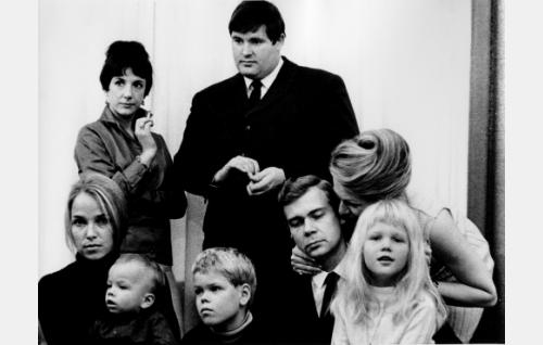 """Rouva Saxén (Heidi Krohn), nuori sosiologi """"Sam Tietäväinen"""" (Matti Siitonen), Helinä (Eija Pokkinen) ja Pentti Lehmusto (Risto Aaltonen) sekä kampaamon omistaja Gertrud Kaira (Mai-Brit Heljo). Kuvan lapset ovat jääneet tunnistamatta."""
