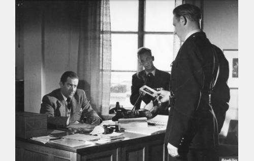 Pöydän ääressä komisario Laine (Kaarlo Halttunen).