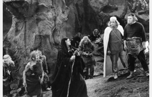 Ilmarinen (Ivan Voronov, oik.) ja Lemminkäinen (Andris Ošin) ovat saapuneet Pohjolaan. Heitä vastassa on Pohjolan emäntä Louhi (Anna Orotško).