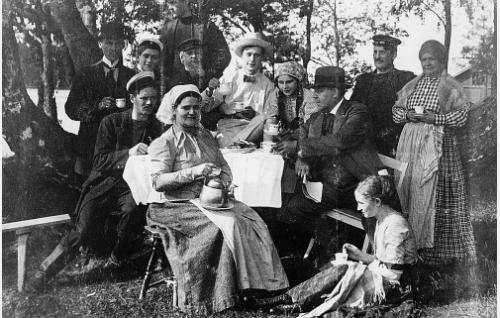 Kahvitauko Nuoren luotsin kuvauksissa. Pöydän ääressä oikealla istuu Kaarle Halme, vasemmalla hänen vieressään Hilma Rantanen ja takana oikealla Konrad Tallroth. Keskellä taustalla parrakas Oskar Krabbe, edessä kahvipannu sylissään Mia Backman.