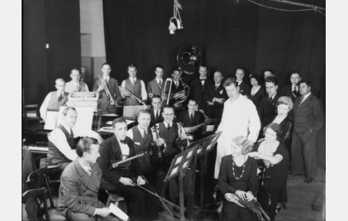 Musiikin säveltäjä, orkesterin ja lauluryhmän johtaja Georg Malmsten seisoo valkeassa asussa.